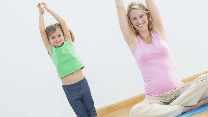 ママと一緒に身長を伸ばす体操をする幼児