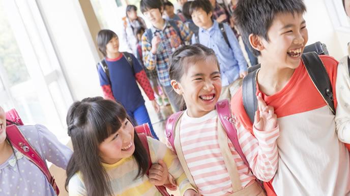 学校の友達と話しながら下校する小学生