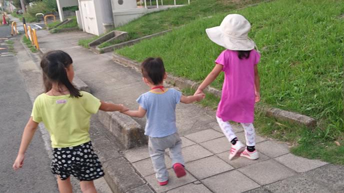 二人の姉に手を引かれる弟