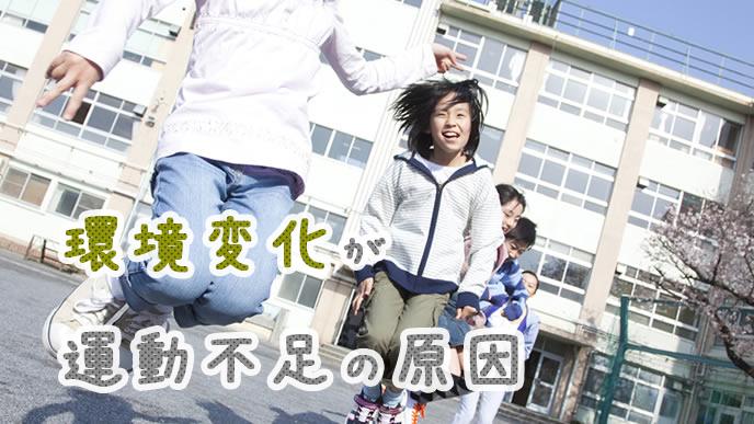 校庭で大縄跳びをする小学生