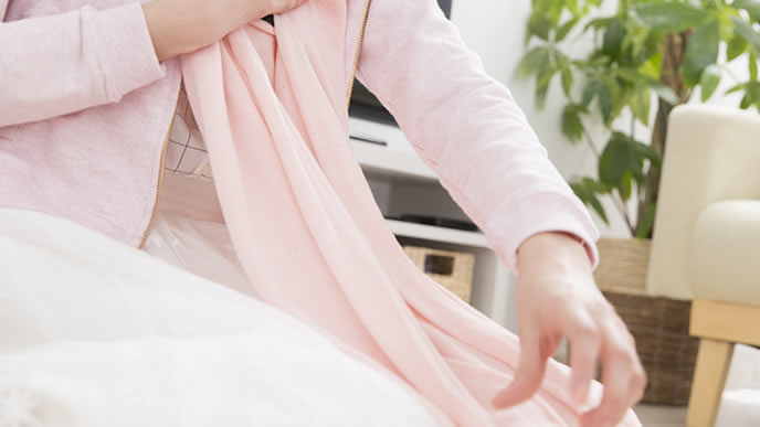 乾いた洗濯物を畳む主婦