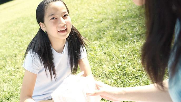 ママと公園でお昼を食べる女の子