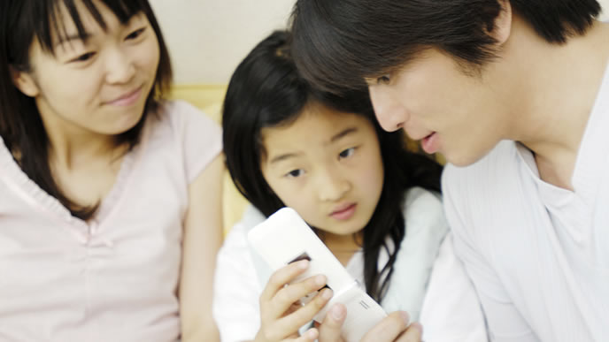 携帯電話をパパに見せる女の子