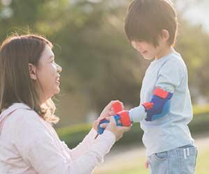 子供の腕にプロテクターを付けてあげる母親