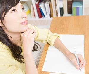 ノートに書き物をしながら考える女性