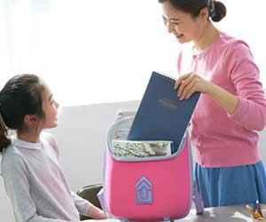 子どものバッグに荷物を入れる母親