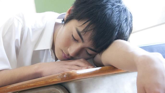 授業中に居眠りする男子中学生