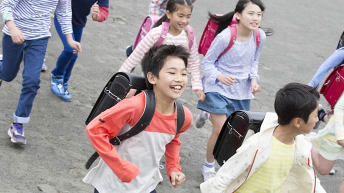 校庭を走る遊びに夢中の小学生