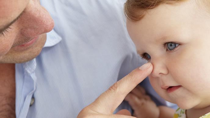 赤ちゃんの視覚と聴覚を確かめる医師