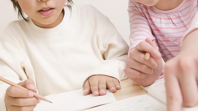 姉に鉛筆の持ち方を教わる小学生