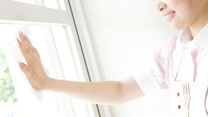 雑巾で窓を拭く専業主婦