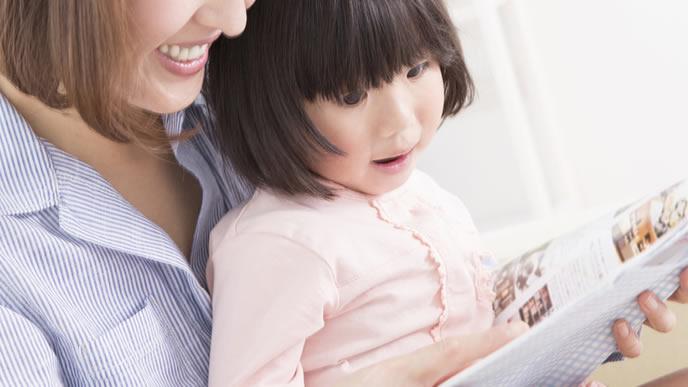 ママと一緒に図鑑を読む女の子