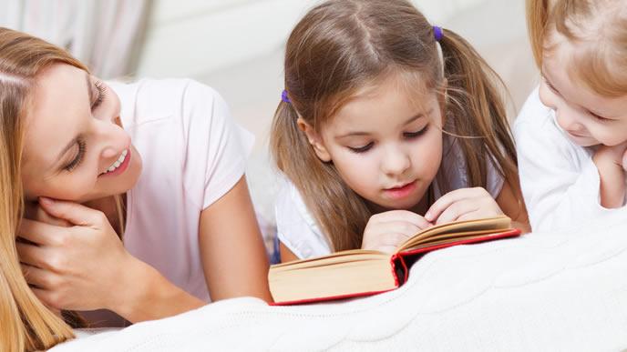 ママと妹と一緒に絵本を読む姉