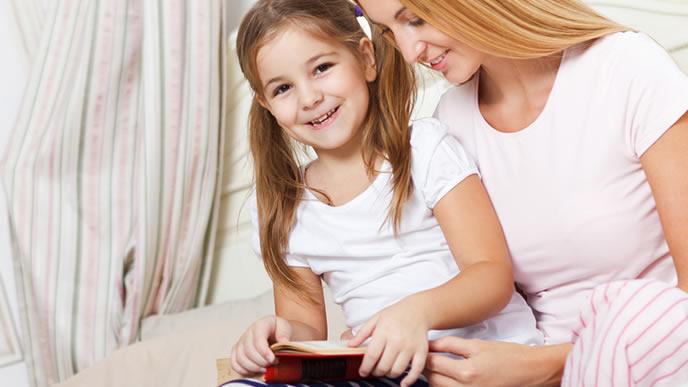 ママに絵本を読んでもらい喜ぶ女の子