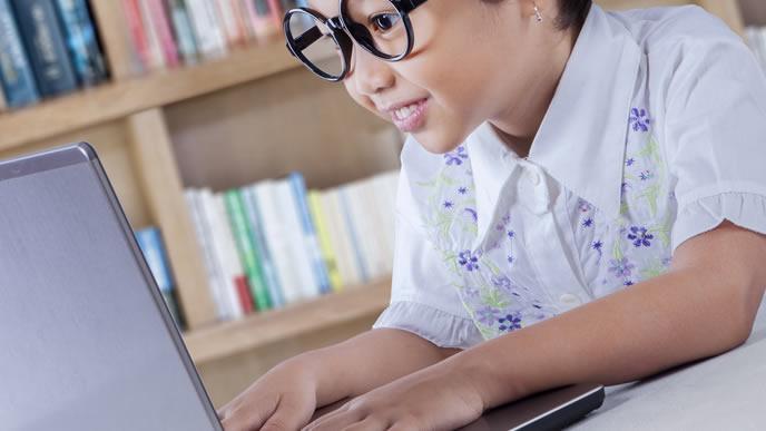ノートパソコンでプログラミングを勉強する男の子