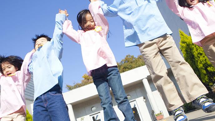 お友達と一緒に手を繋いでジャンプする園児