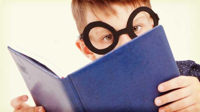 本を読んでいる眼鏡をかけた少年