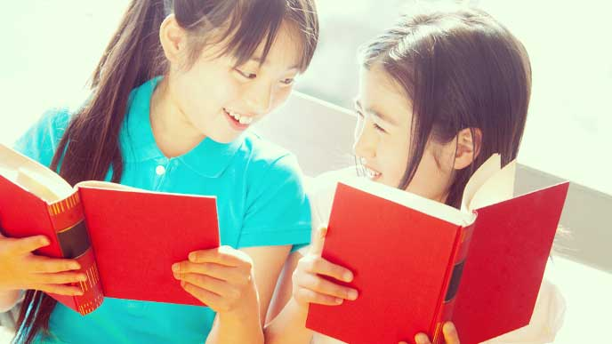 友達同士で一緒に本を読んでいる女の子達