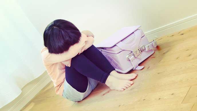 落ち込んで体育座りしている小学生の女の子