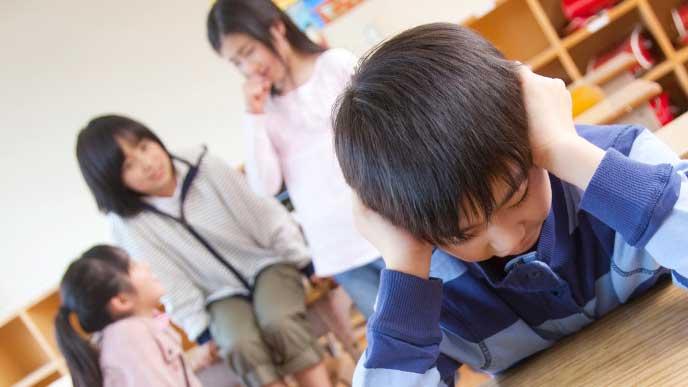 小学校のクラスの子達から陰口を叩かれ耳を塞いでいる男の子