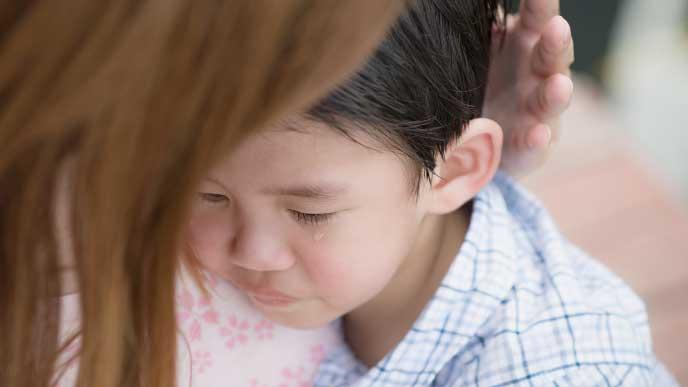 泣いてる子供を抱きしめている母親