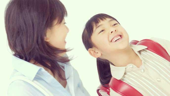 笑顔で母親と話してるランドセルを背負った女の子