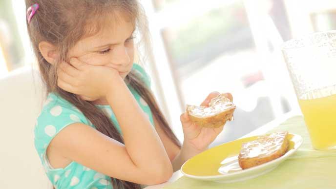 肘をついてパンを食べてる女の子