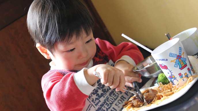 レストランでスプーンとフォークを使ってハンバーグを食べてる男の子