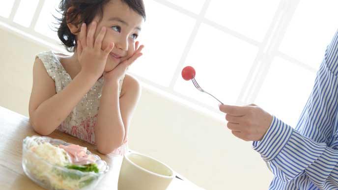 母親にトマトを進められたけど笑って誤魔化そうとしている女の子