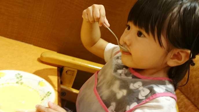 姿勢良く座りスプーンでスープを飲んでる女の子