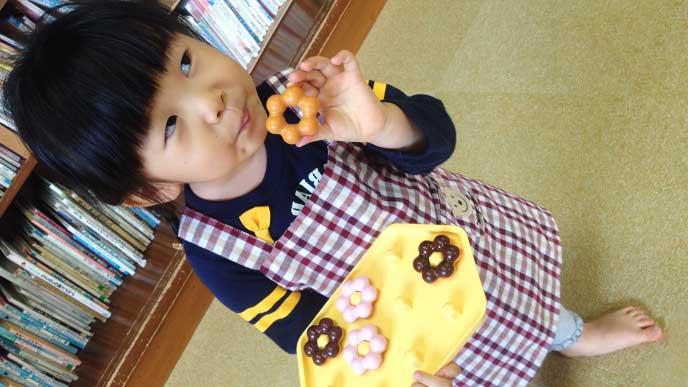 立ちながらドーナツを食べてる女の子