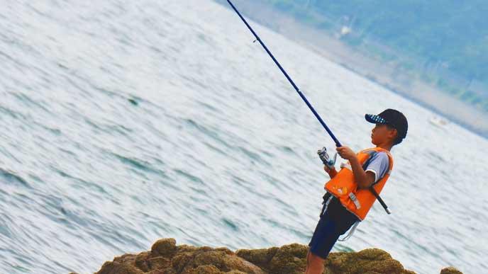ライフジャケットを着て海で釣りをしている少年