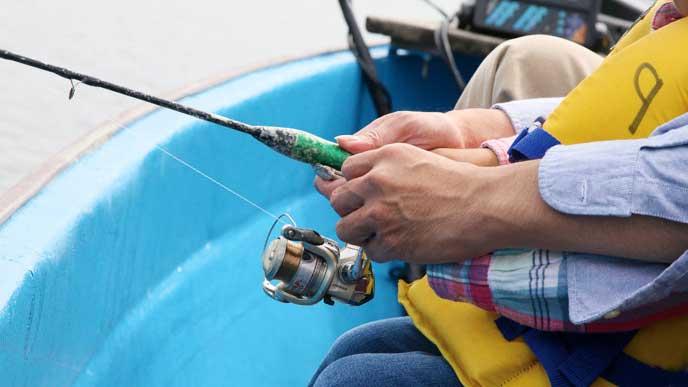 大人に釣りの仕方を手を持って教えてもらっている子供
