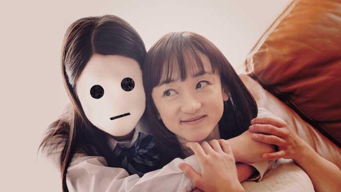 無表情の仮面をつけて母親に後ろから抱きついている女の子