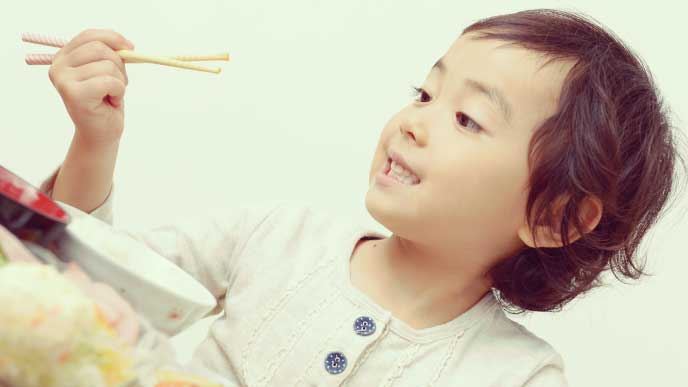 箸の持ち方を練習している女の子