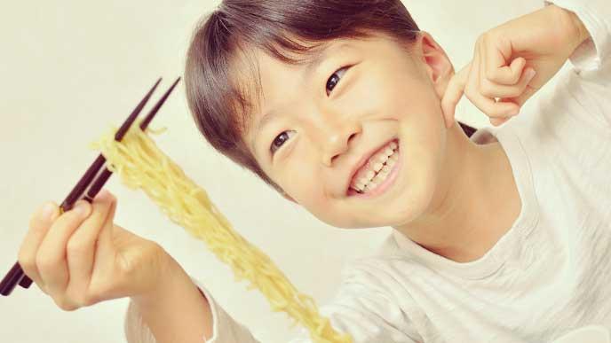 沢山のラーメンを箸で持ち上げている女の子