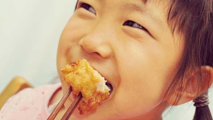 刺し箸でフライドチキンを食べている女の子