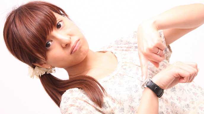 右手につけた腕時計を指差し困った顔をしている女性