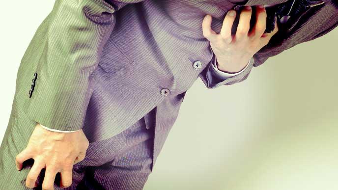 緊張で胸と膝を押さえているスーツを着た男性