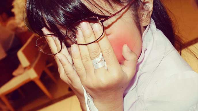 恥ずかしくて赤くなった顔を手で覆っている女の子