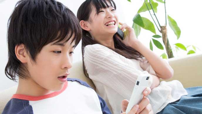 携帯ゲームで遊んでる男の子と友達に電話してる小学生の女の子