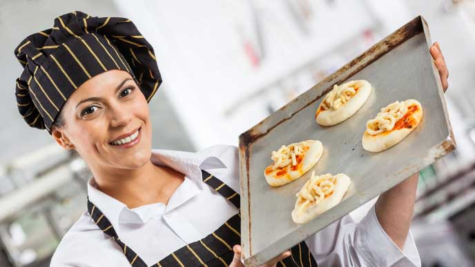 小さなピザを作ってる女性