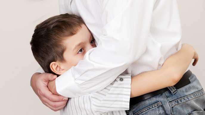 恥ずかしがって母親に抱きついている男の子