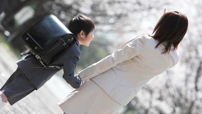 母親に手を引かれて歩いているランドセルを背負った小学生の男の子