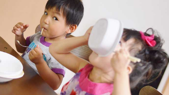 お皿を口につけて一気にパスタを食べてる女の子と少しずつ食べてる男の子