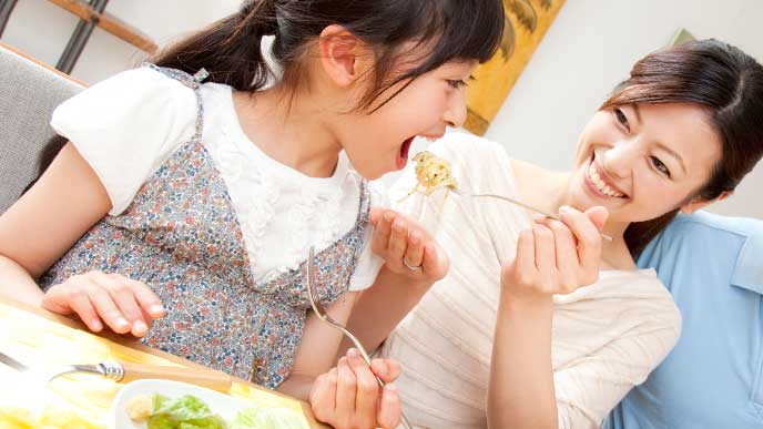 母親から「アーン」で食べさせてもらってる女の子