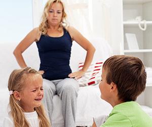喧嘩する子供を怒って睨み付ける母親