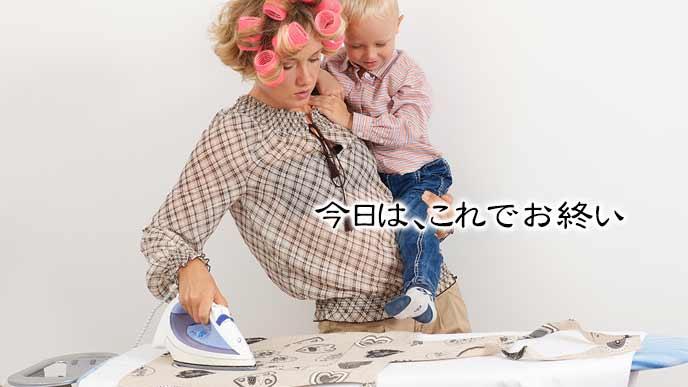 子供を抱きかかえながらアイロンをかける主婦