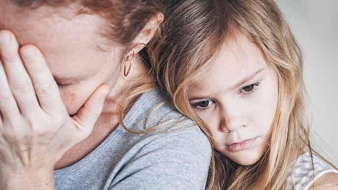 後悔して塞ぐ母親と背中に抱きつく子供