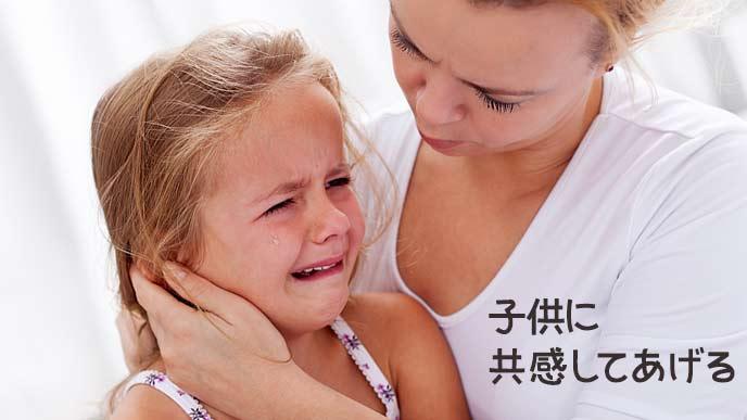 泣く子供をなだめて抱く母親